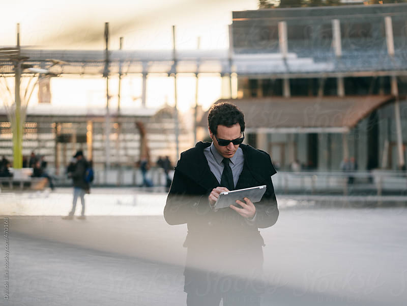 Young businessman using digital tablet in the financial district by Davide Illini for Stocksy United