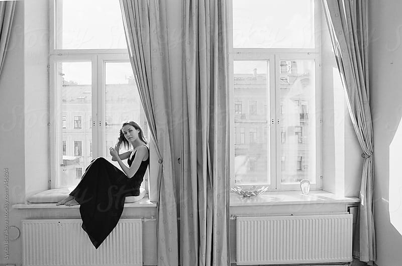 Woman fixing her hair while sitting on a windowsill by Lyuba Burakova for Stocksy United