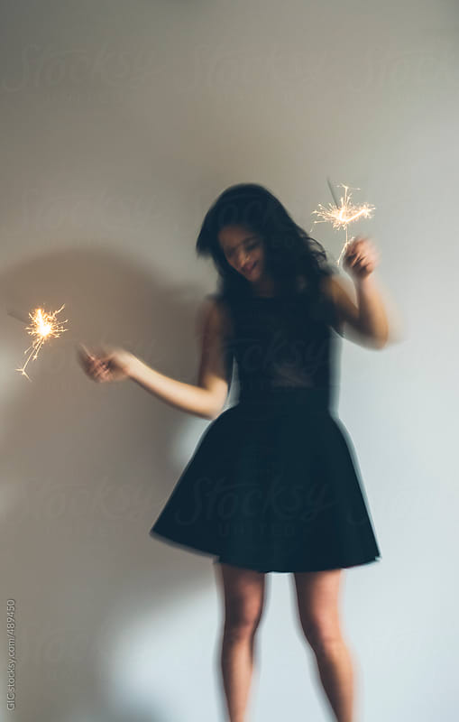 Happy woman holding sparkler during a party by GIC for Stocksy United