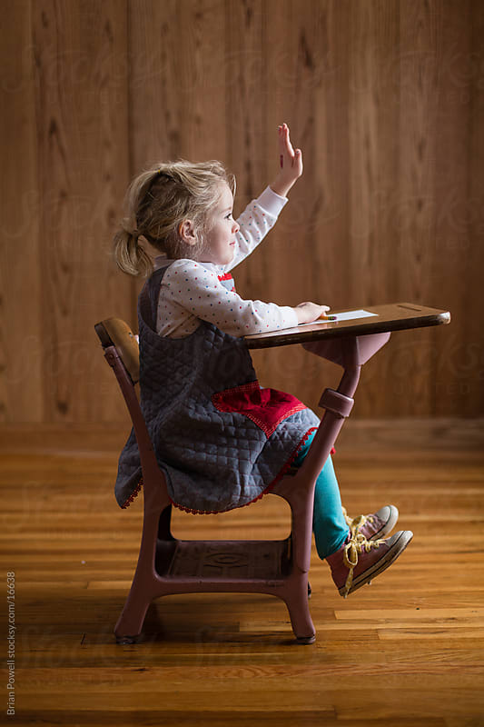 Little girl raising hand at school by Brian Powell for Stocksy United