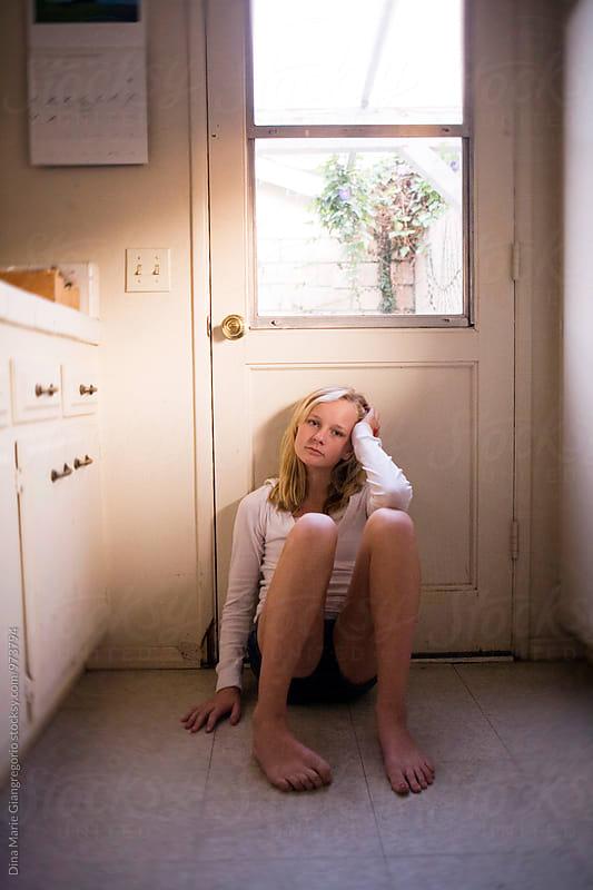 Teenager Sitting On Kitchen Floor Up Against Door by Dina Giangregorio for Stocksy United