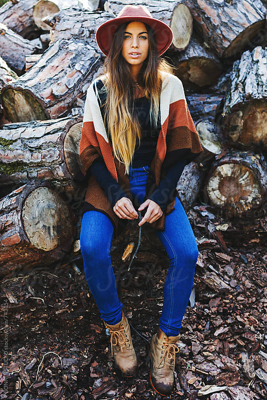 Hipster woman sitting in front of a stack of trunks. by BONNINSTUDIO for Stocksy United