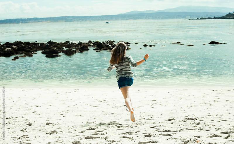 Teen girl running toward the ocean in Monterey by Carolyn Lagattuta for Stocksy United