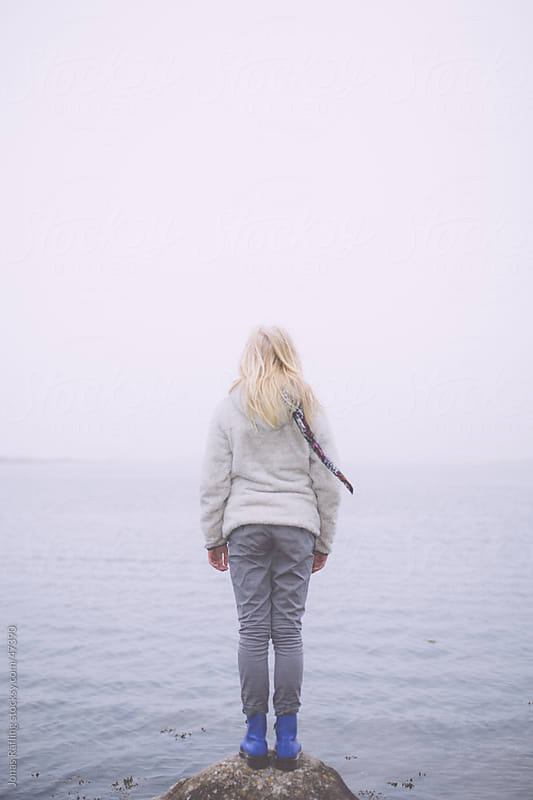 Girl standing on a stone looking out on the foggy sea by Jonas Räfling for Stocksy United