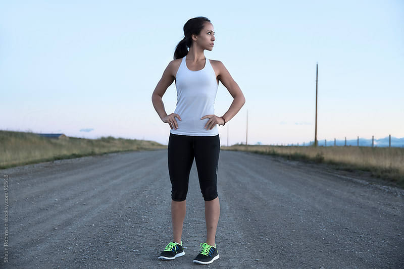 A young fit woman standing on a gravel road by Shaun Robinson for Stocksy United