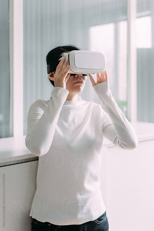 Woman wearing virtual reality headset by Maa Hoo for Stocksy United