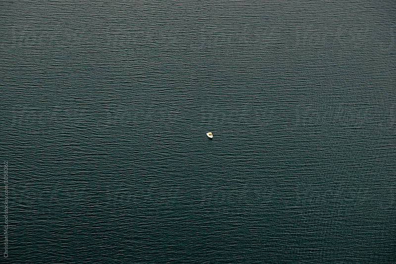 solitary boat on a lake in iceland by Christian McLeod Photography for Stocksy United