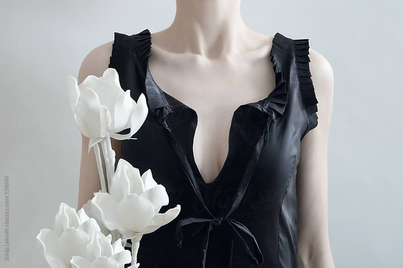 woman in black dress with white flowers by Sonja Lekovic for Stocksy United