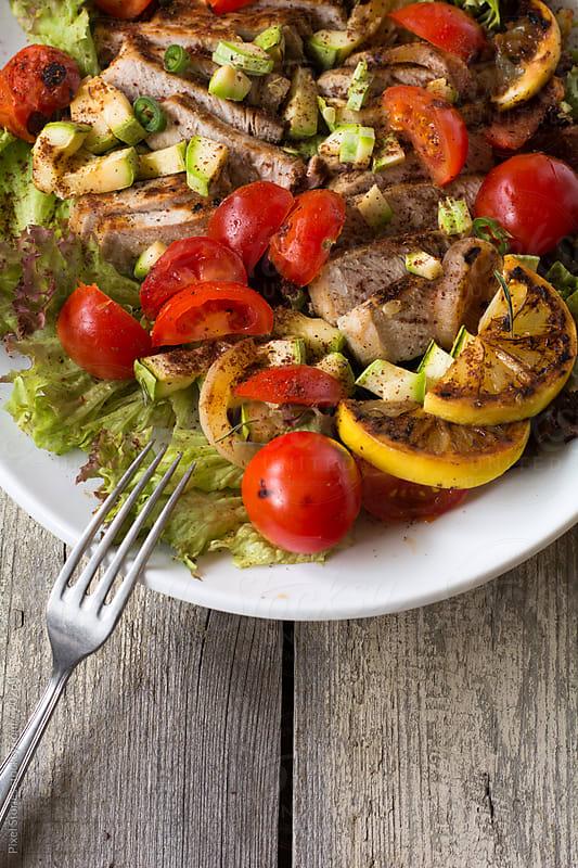 Food: grilled sliced pork with grilled vegetables salad by Pixel Stories for Stocksy United