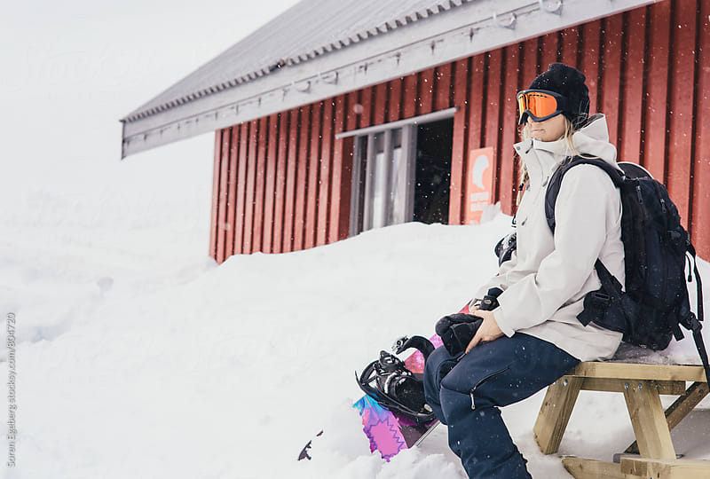 Female snowboarder sitting in the snow holding snowboard by Søren Egeberg Photography for Stocksy United