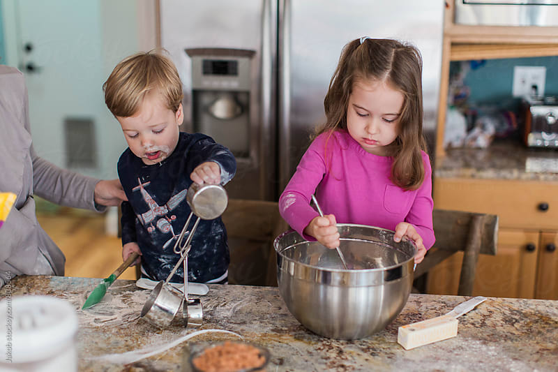 Mother, big sister and little brother making cookies in a kitchen by Jakob for Stocksy United