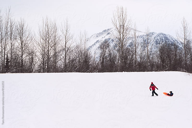 parent pulling child in a sled toward the top of a snow covered hill by Tara Romasanta for Stocksy United
