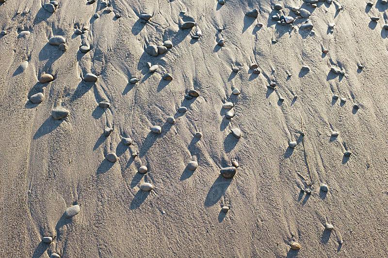 Detail of rocks on beach, casting long shadows by Paul Edmondson for Stocksy United
