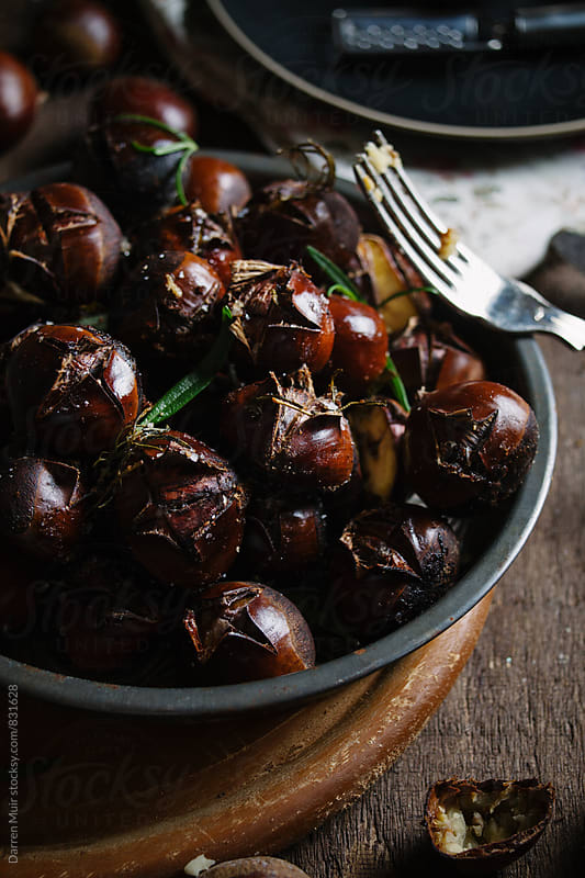 Roasted chestnuts with rosemary. by Darren Muir for Stocksy United