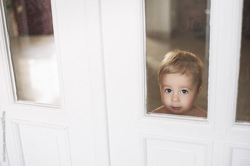 Cute little boy peeking through a door by Lea Csontos for Stocksy United