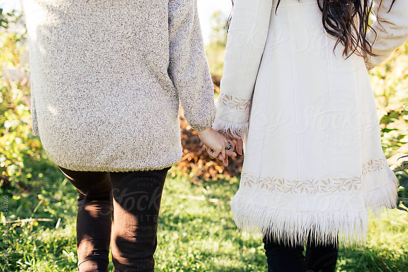 Two best friends holding hands walking on a fall day  by HOWL for Stocksy United