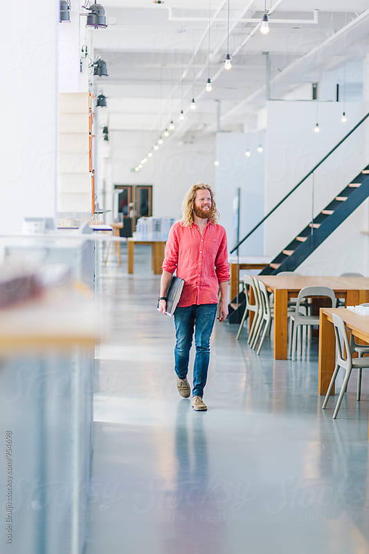 Young designer walking in a spacious beautiful office or studio. by Ivo de Bruijn for Stocksy United