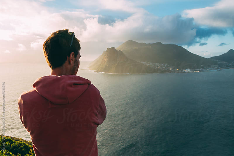 Back view of a young man on a lookout looking at the sea coast at sunset by Alejandro Moreno de Carlos for Stocksy United
