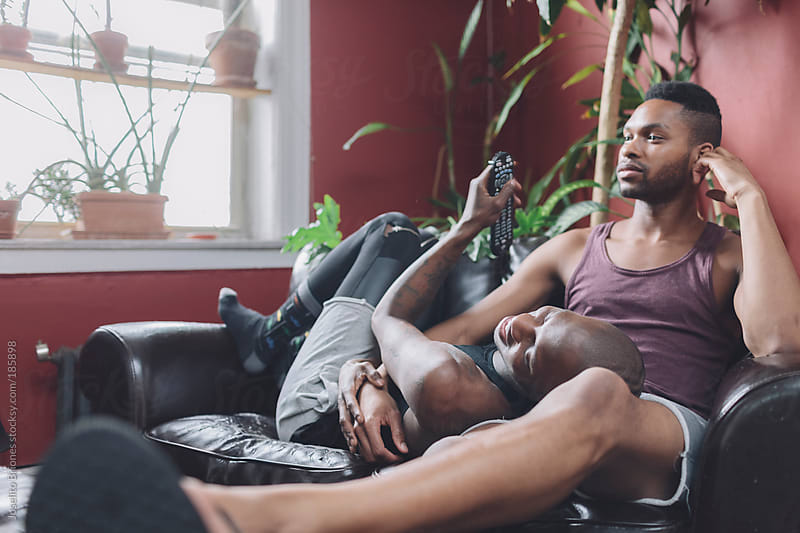 Gay Couple Watching TV at Home by Joselito Briones for Stocksy United