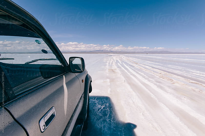 Car crossing salt flat on adventure travel. First person point of view by Alejandro Moreno de Carlos for Stocksy United