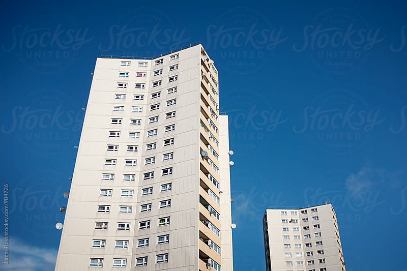 Two tower blocks against bright blue sky by James Ross for Stocksy United