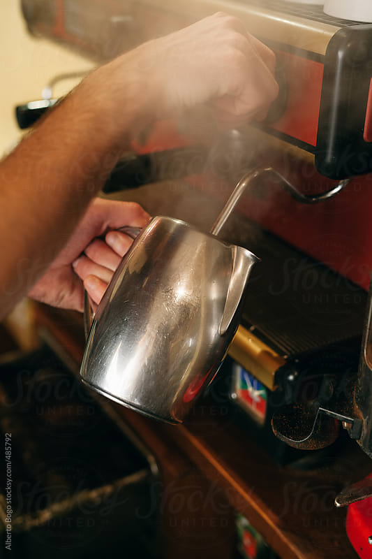 A barista making coffee at an espresso machine by Alberto Bogo for Stocksy United