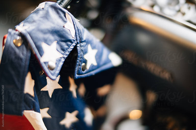 Shallow Depth of Field Photo of Leather American Flag Jacket on Motorcycle Handle by Austin Rogers for Stocksy United