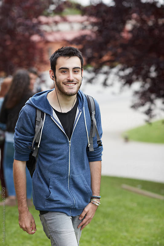 Portrait of young man with backpack at the campus by Miquel Llonch for Stocksy United