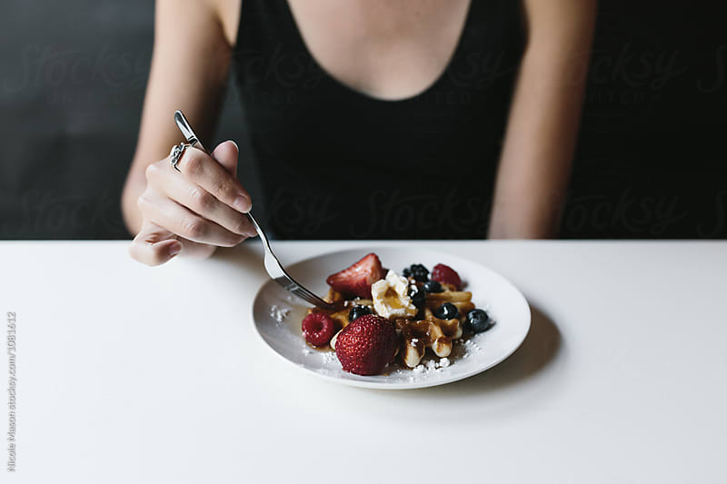 person eating waffle with fruit and butter on top by Nicole Mason for Stocksy United