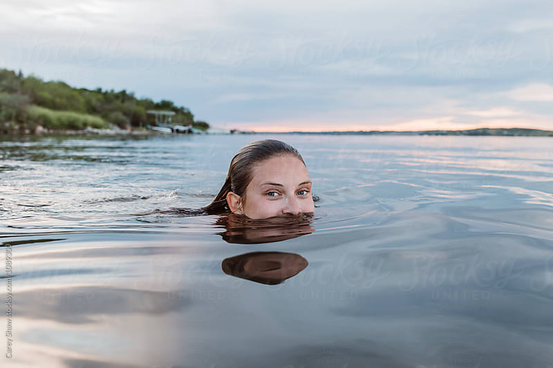 Beautiful young woman swimming in lake at dusk by Carey Shaw for Stocksy United