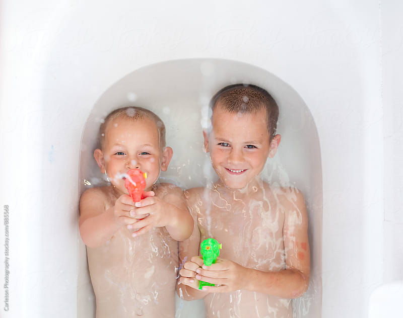 Brothers with squirt guns in the bathtub by Carleton Photography for Stocksy United