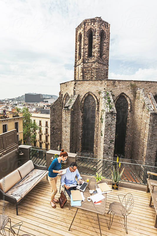 Business teamwork working on a beautiful outdoor workspace near a beautiful Romanic Cathedral. by BONNINSTUDIO for Stocksy United