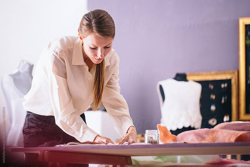 Young woman working on a paper model by michela ravasio for Stocksy United