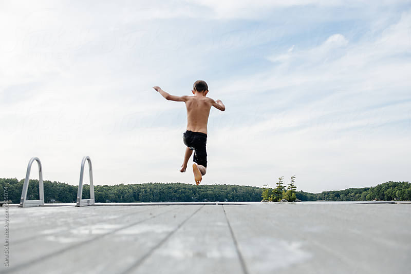 Boy jumps off dock into a lake by Cara Dolan for Stocksy United