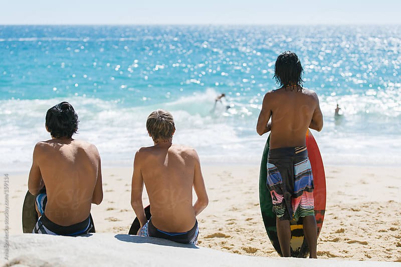 A group of young surfers watching the water on a Mexican beach by Ania Boniecka for Stocksy United
