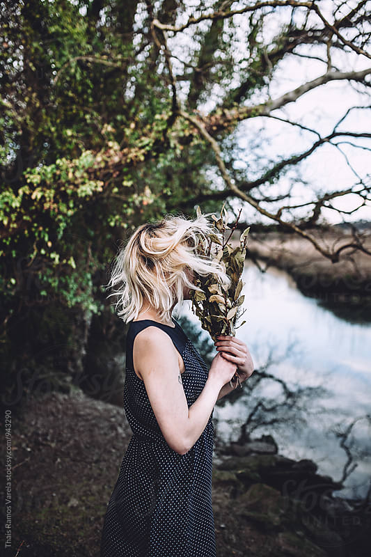 woman hiding her face with a bouquet by Thais Ramos Varela for Stocksy United