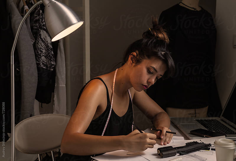 Young Fashion Designer Working in her studio until late hours. by Audrey Shtecinjo for Stocksy United