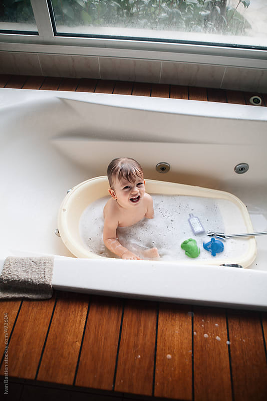 Baby boy taking a bath in a big bathtub by Ivan Bastien for Stocksy United