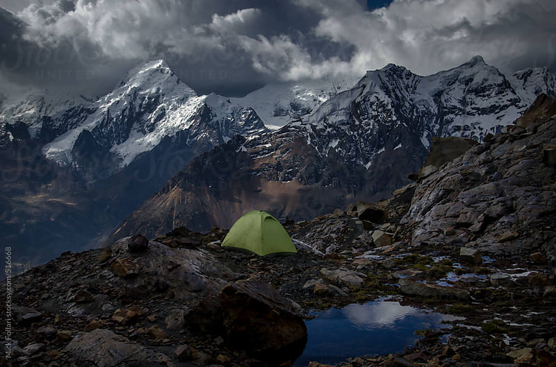 Tent at high altitude with dramatic sky and snow-capped mountains behind by Mick Follari for Stocksy United