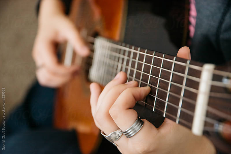 Hands of a young girl playing Spanish guitar by Gabriel (Gabi) Bucataru for Stocksy United