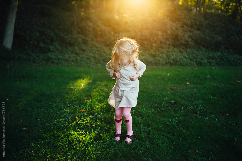 Little Girl Does the Chicken Dance in the Light of the Setting Sun by Amanda Voelker for Stocksy United