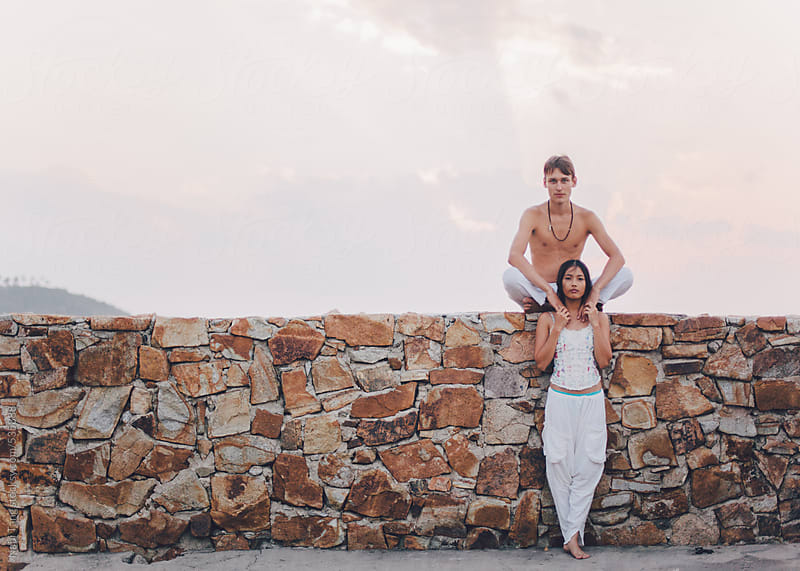 In love couple on the stone wall at sunset time outdoor by Nabi Tang for Stocksy United
