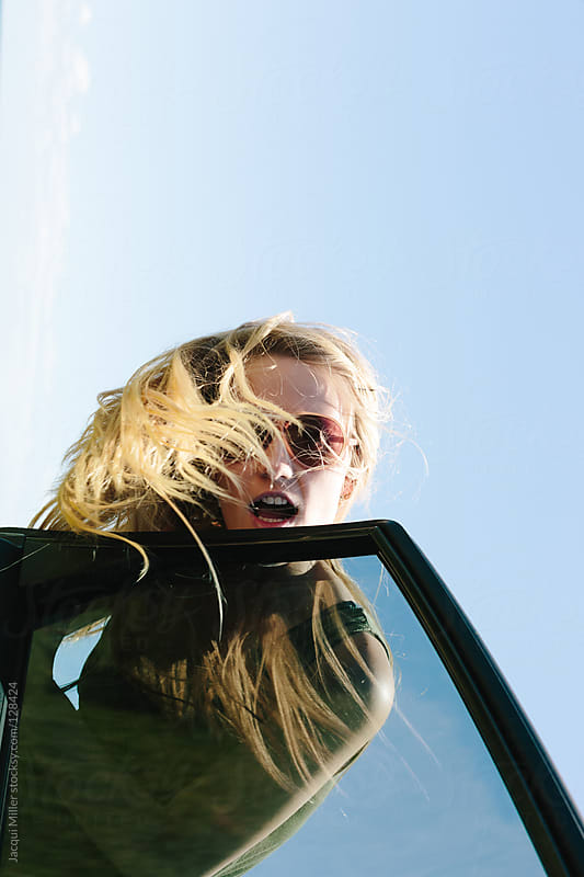 Teenage girl having fun at the car window by Jacqui Miller for Stocksy United