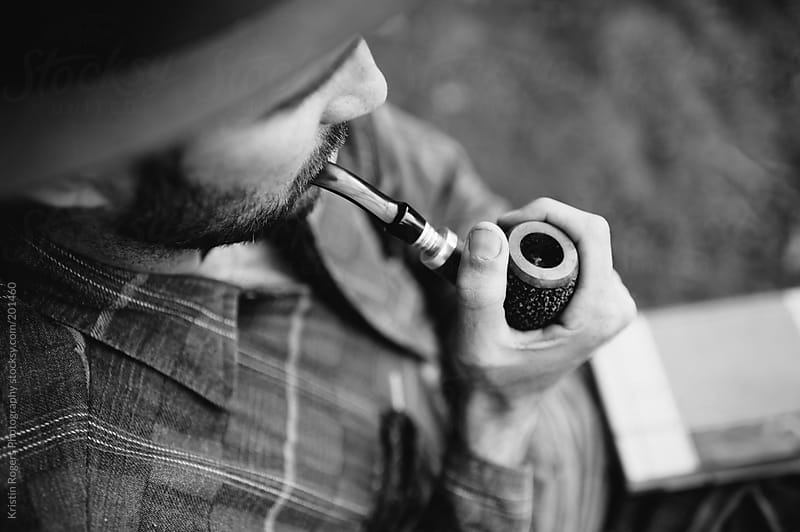 man in hat and flannel smoking a tobacco pipe by Kristin Rogers Photography for Stocksy United