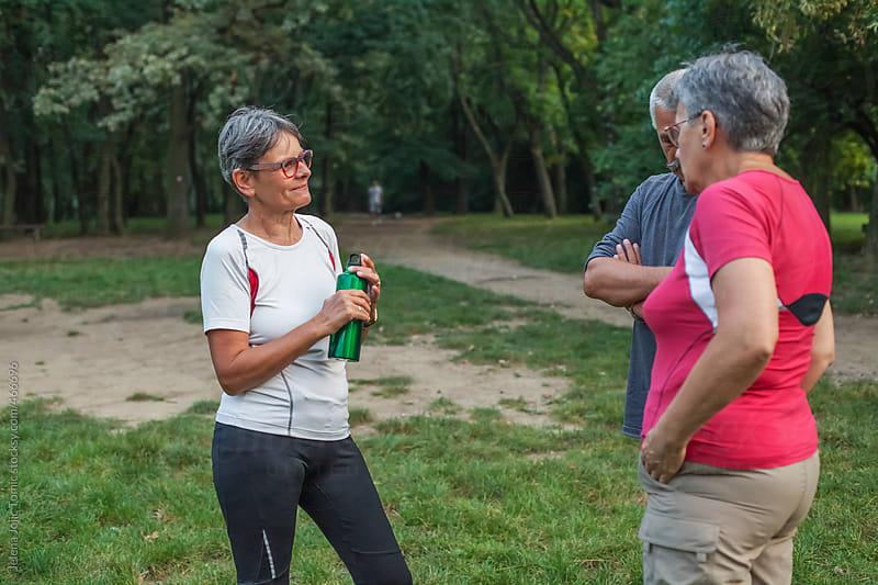Seniors chatting in the park by Jelena Jojic Tomic for Stocksy United