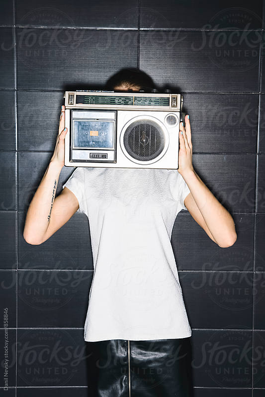 Woman hiding her face from the tape-recorder against of black background by Danil Nevsky for Stocksy United