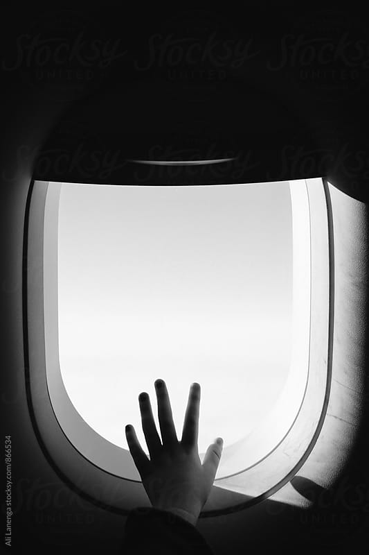 Fingers at the window seat by Ali Lanenga for Stocksy United