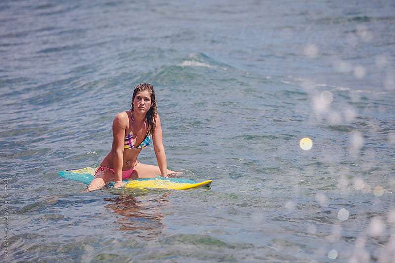 Female surfer sitting on her board waiting for a wave. by Shelly Perry for Stocksy United