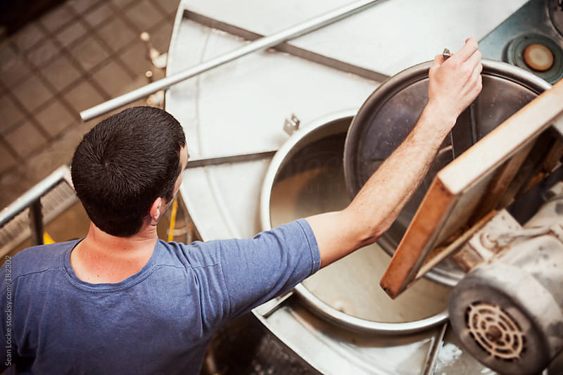 Beer: Brewer Checks Process In Mash Tun by Sean Locke for Stocksy United