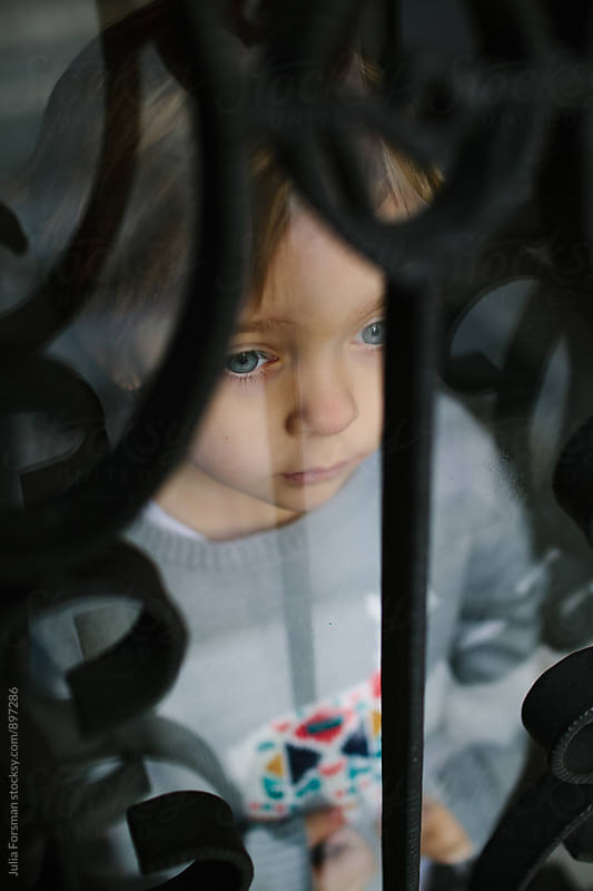 Little girl waits patiently behind a barred window looking at the big world outside. by Julia Forsman for Stocksy United